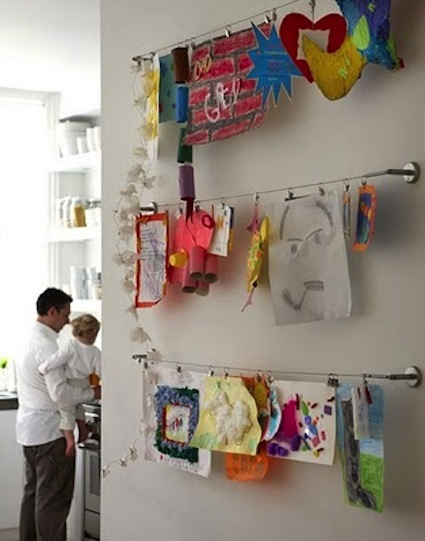Organize kids artwork by hanging an Ikea shower string on a wall