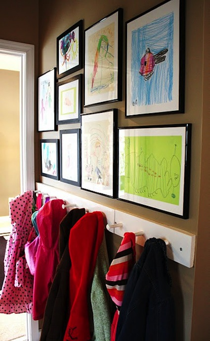 Gallery wall of kids art above a coat rack